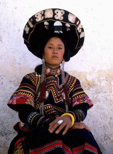 Nuosu Yi 3. A young Suondi mother from Butuo County wears the traditional flat-toped hat with stamped silver plates, the under- and over- jacket comobination, lined with modern print cloth, dangly silver earrings, a woven wool pleated skirt and a saddle-shaped silver ring.  Photo by Zhong Dakun
