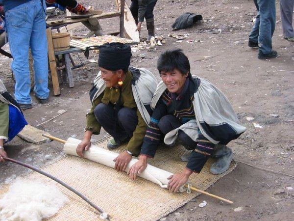 Nuosu Yi 2. Making felt: rolling the felt before final drying.  Both men wear Yynuo-style woven wool  vala capes.  The man on the left  has an imitation coral and amber mohne earring and a tradition Yynyo style turban with horn.  The man on the right wears a jacket with Shynra-style inset decoration.  At the bottom of the picture to the left raw wool is being fluffed with the fluffing-bow. Photo by Stevan Harrell
