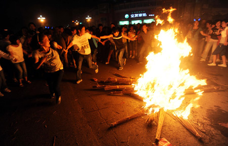 People dance around the bonfire during the torch festival in Xichang, capital of Liangshan Yi autonomous prefecture, Sichuan province, August 15, 2009. The festival is also called the Oriental Valentine