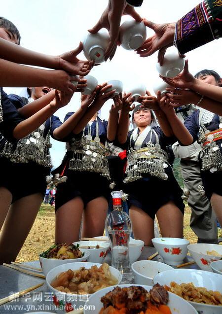 城子古村参加婚俗表演活动的哈尼族姑娘在相互敬酒(10月18日摄)