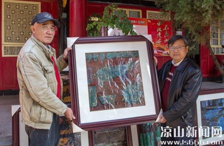 卢德富将12幅彝族漆版画捐赠给州奴博。 记者 钟玉成 摄