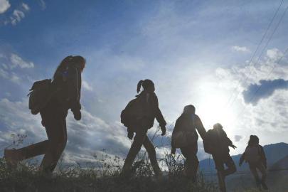 山间路上,孩子们背着书包迎着朝阳向学校走去。