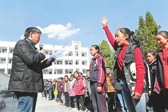 2月25日,越西县南箐镇中心小学开学典礼上,校长耿道杨拿着学籍名册逐一点名。 记者 李向雨 摄