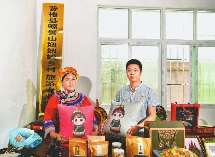 唐举帅(右)与村民博什么日洛(左)拿着新设计的文创抱枕在展览室里。