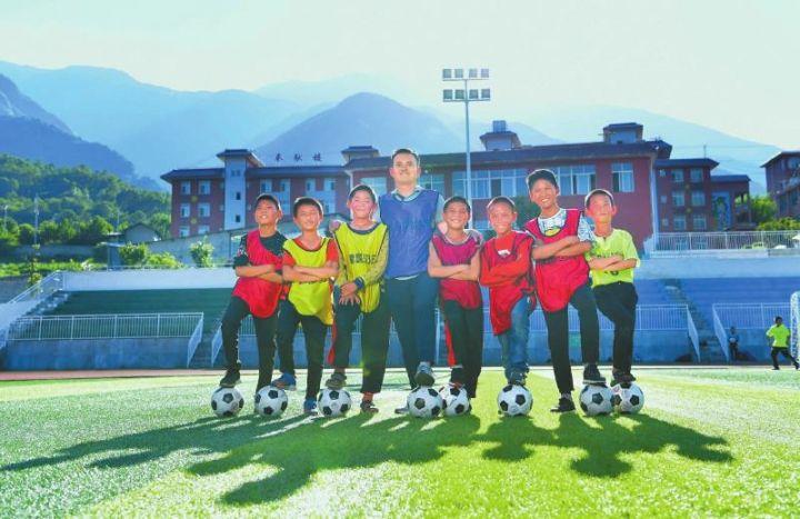 陈庚(左四)与部分足球小队员一起。