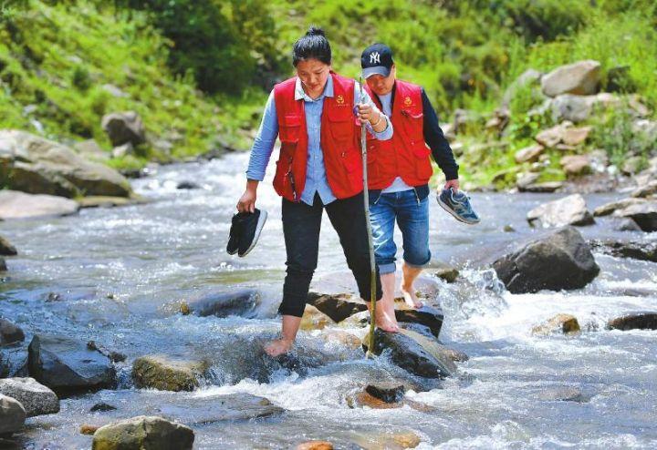 杨卓玛(前)与队员一起下乡走访。