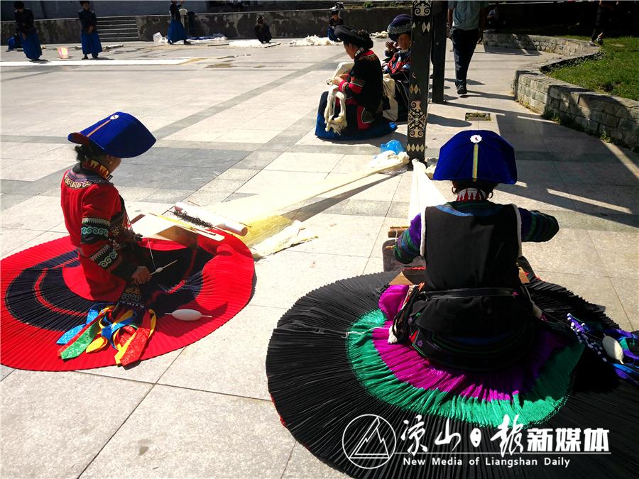 身着民族盛装的彝族妇女正在纺织.jpg