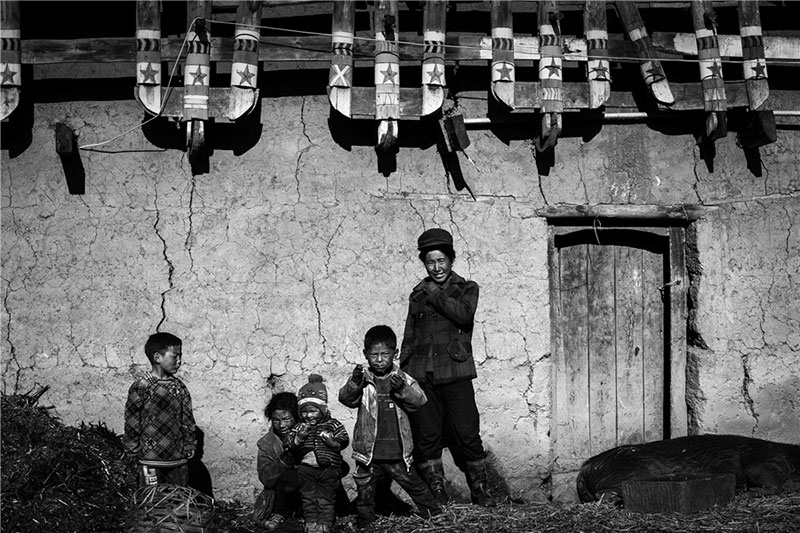 A family poses in front of their home. Photo by He Qinming. [Photo provided by photoint.net]
