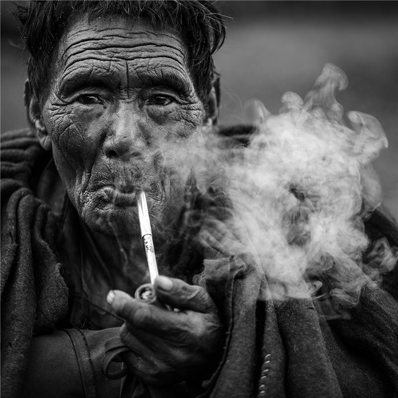 Portrait of an old man of Yi ethnic group smoking. Photo by Liu Jianming. [Photo provided by photoint.net]