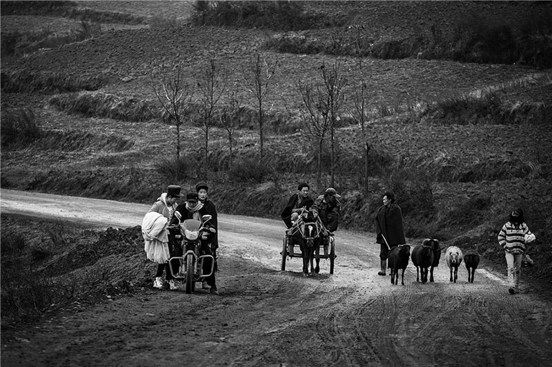 Motorbike and horse-drawn vehicles seem to be the major means of transport in the mountainous area where Yi people live. Photo by Liu Jianming. [Photo provided by photoint.net]
