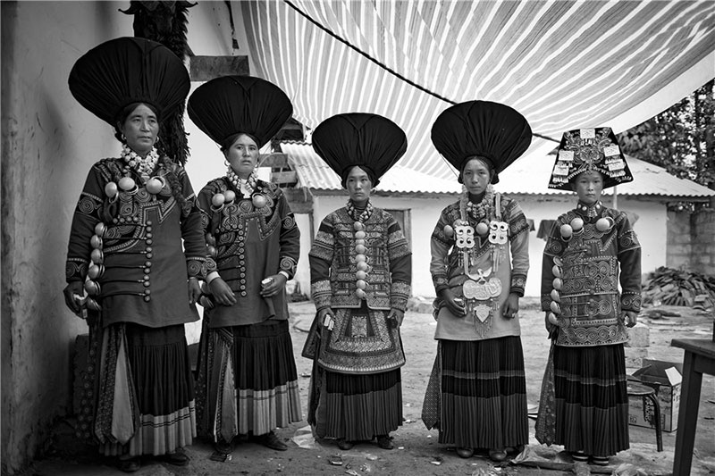 Women from the Yi ethnic group wear traditional costumes and headwear. Photo by He Qinming. [Photo provided by photoint.net]