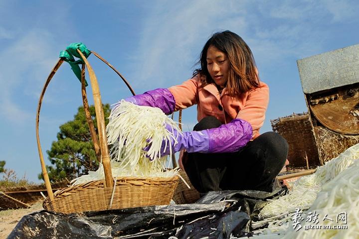 2018年 2月12日。云南省峨山县小簪土村。一名在外打工的姑娘回家帮忙晾晒萝卜丝。