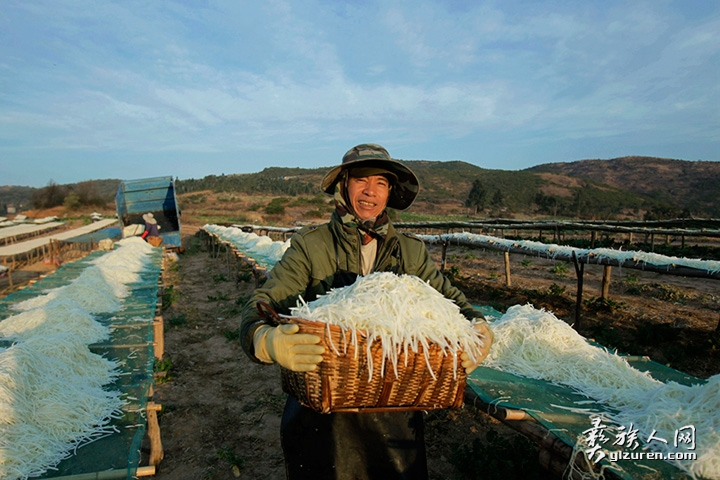 2020年 1月20日。云南省红塔区小坝村。一位男子正在用竹箩端着萝卜丝倒在晾床上,进行晾晒。