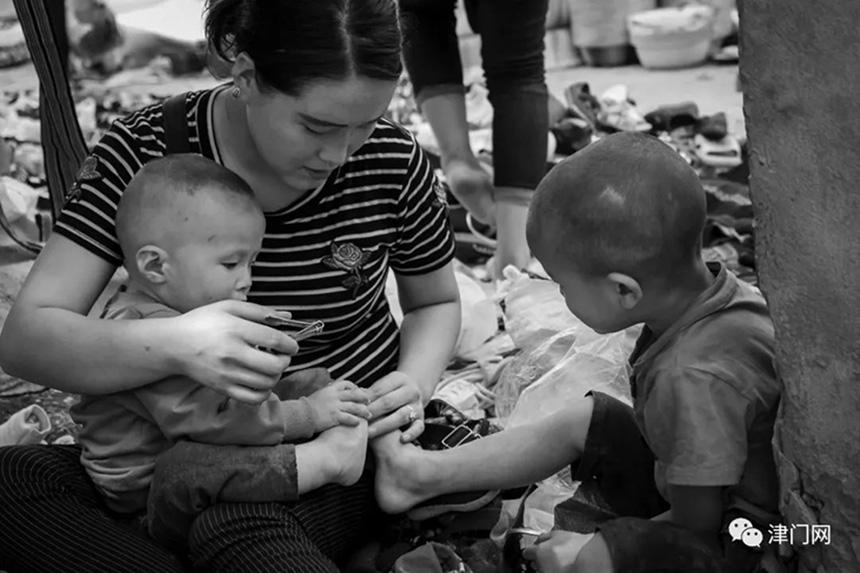 细心的妈妈为孩子修剪指甲。