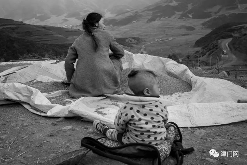 带着孩子亮晒苦荞的母子。