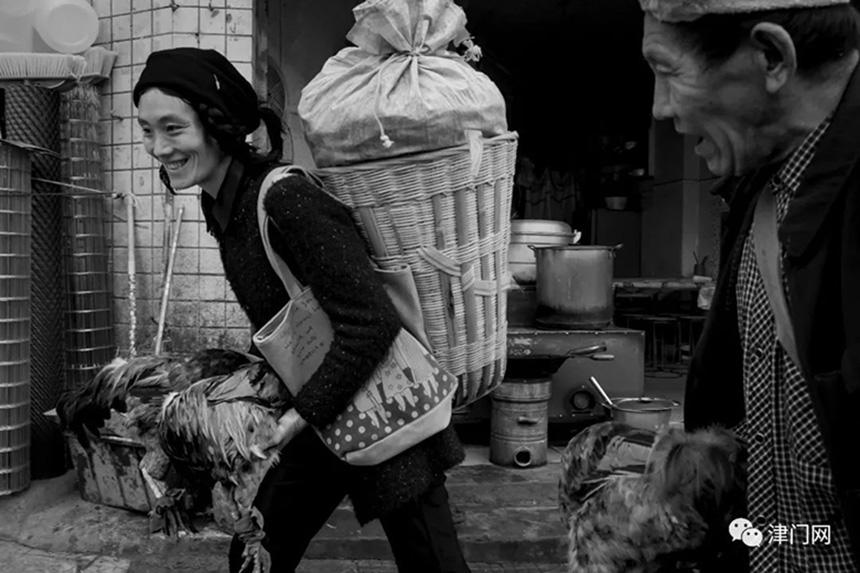 背着自产粮,手捉跑山鸡的彝族大妈准备到集市去交易。