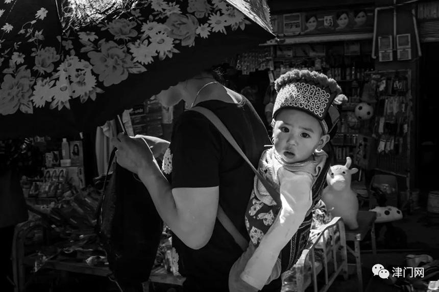 打着阳伞、衣着时尚的妈妈背着身穿彝族传统服装的孩子赶集。