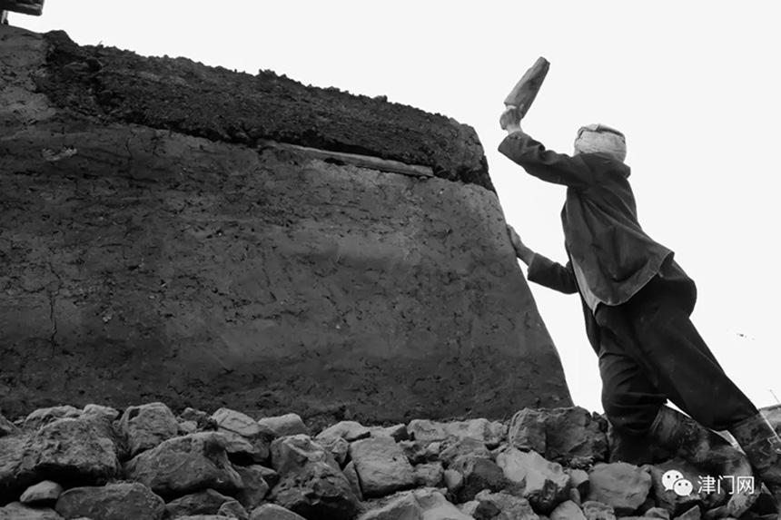 彝族老汉正在用彝族古老的工艺加固院墙。