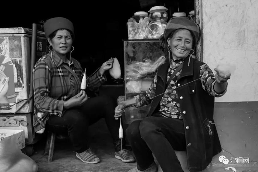 甜美、幸福的彝族妇女在做针线活。