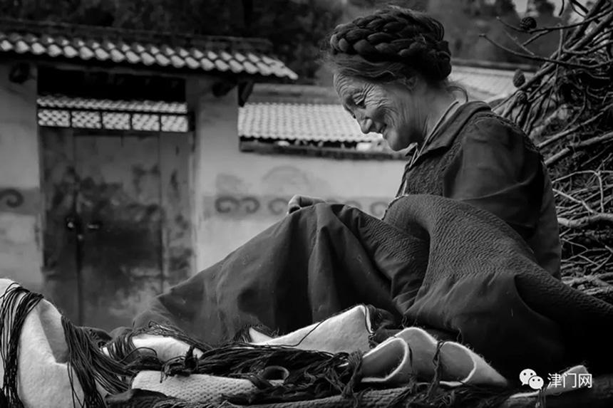 慈祥、温情的彝族大妈正在编织美好的生活。