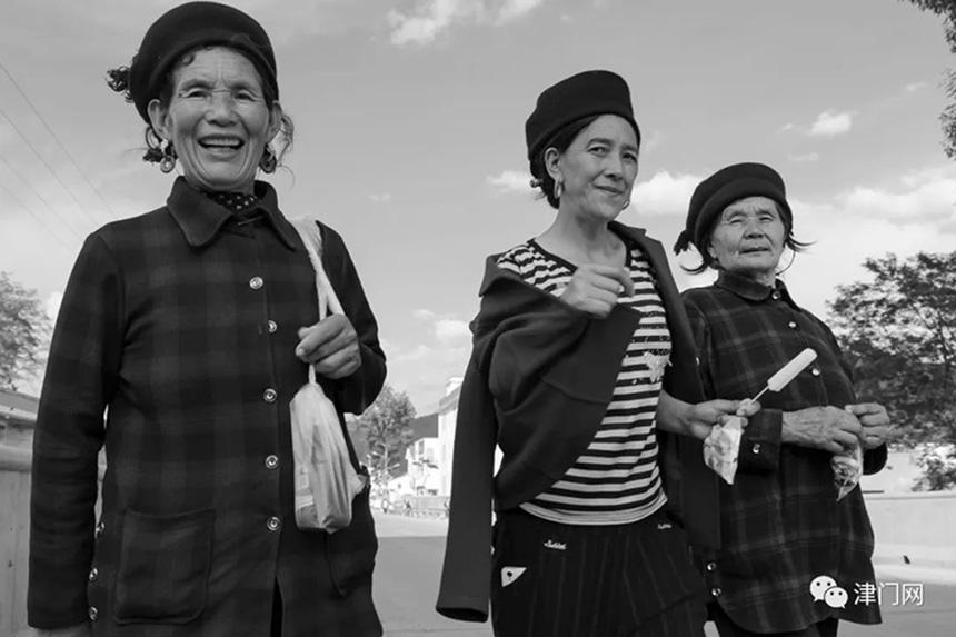 手拿冰棍,开开心心去赶集市的彝族姐妹。