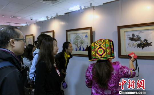 """10月24日,内地及港澳青年艺术家在成都观赏""""杨华珍藏羌织绣作品展""""。图为艺术家聆听导览员讲解相关作品。 张晓曦 摄"""