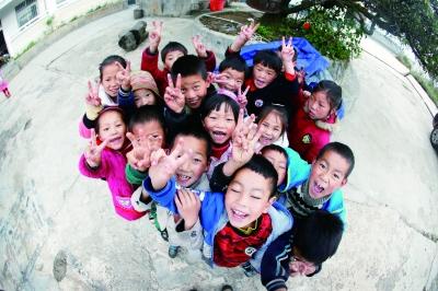 下课后,孩子们开心地围在一起,对着记者的镜头欢笑
